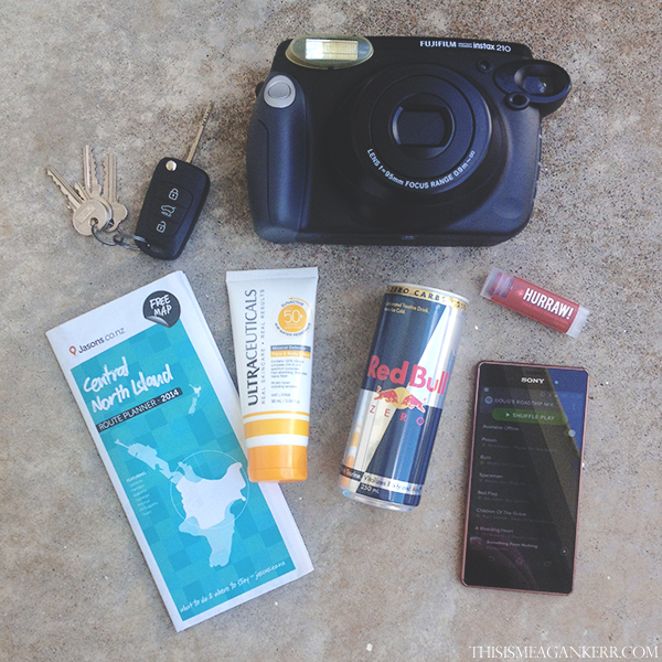 My roadtrip essentials include my Fujifilm NZ Instax Wide 210, a map so I can plan my trip, Ultraceuticals SunActive SPF 50+ Mineral Face & Body Lotion, Red Bull Zero, Hurraw! Balm Black Cherry Tinted Lip Balm and a Spotify playlist